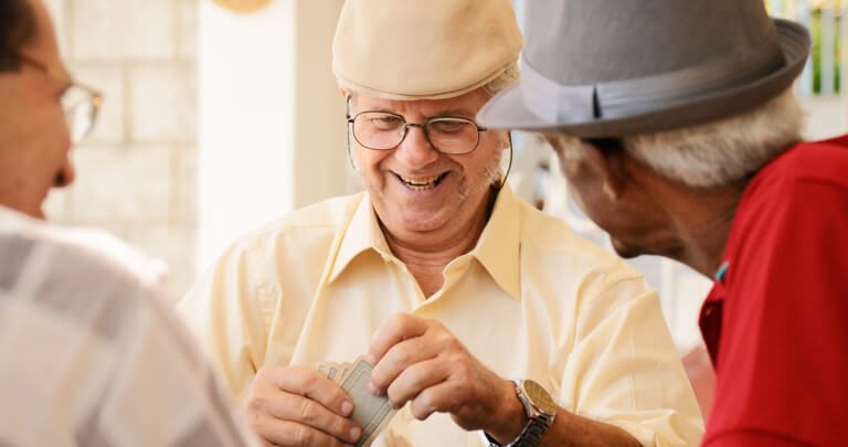 Three elderly men laughing and playing cards